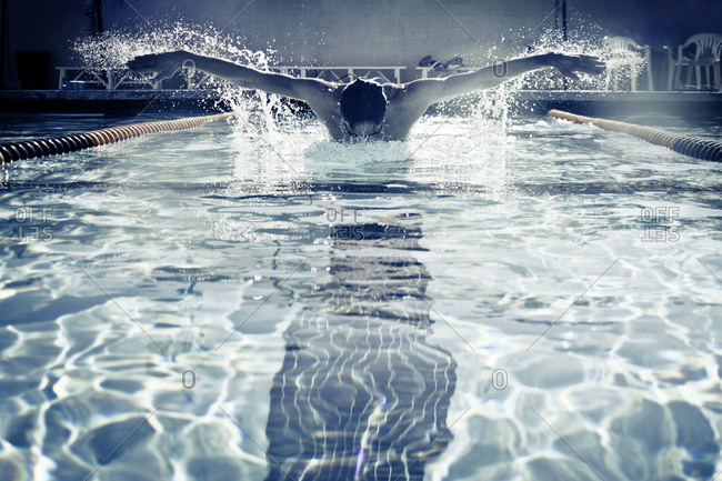 A man swimming the butterfly in pool