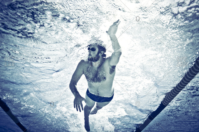 A man swims in a pool lane