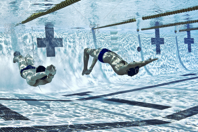 Two men racing underwater
