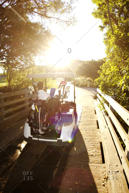 A golf cart crossing a bridge