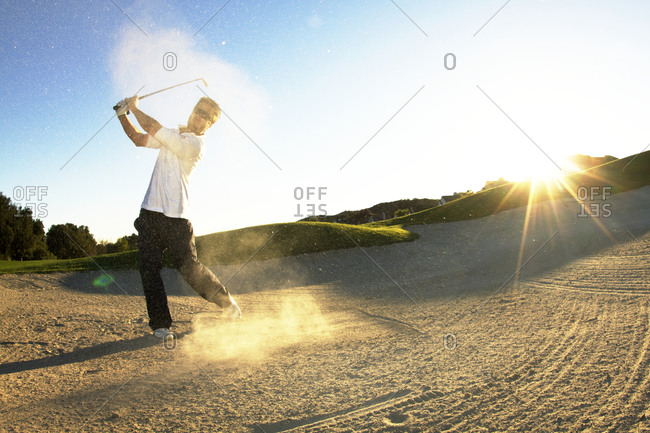 A man hitting golf ball out of sand trap