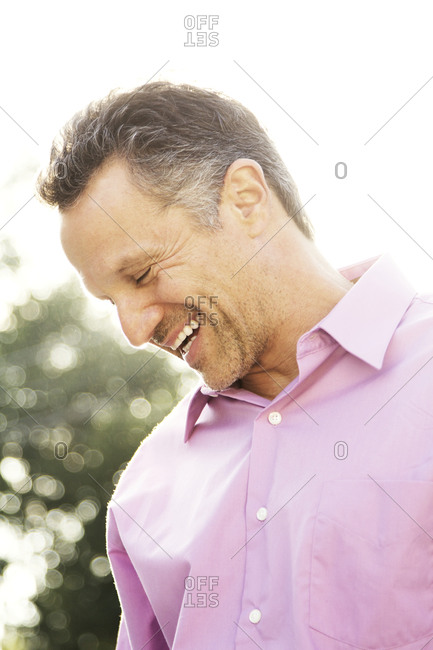 A man laughing outside in sun