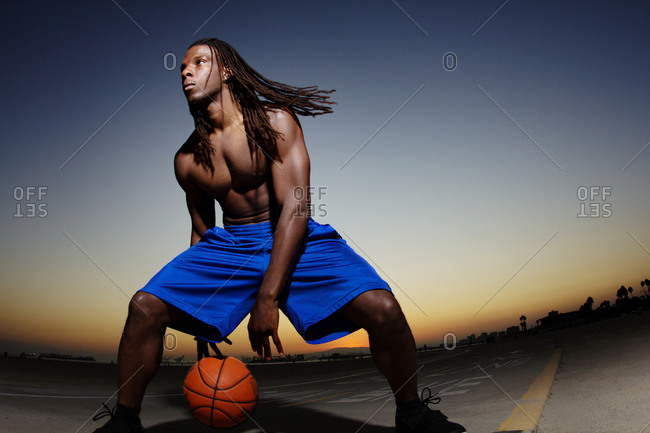 A man dribbling a basketball between his legs