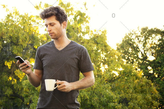 A man stands outside with his phone and coffee