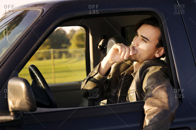 A man leans out the window of his truck