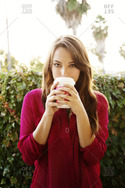 A young woman sips coffee