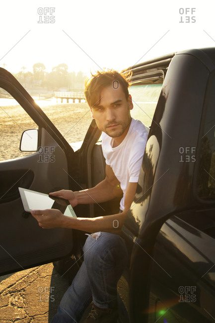 A man leaning out of his truck door with a tablet