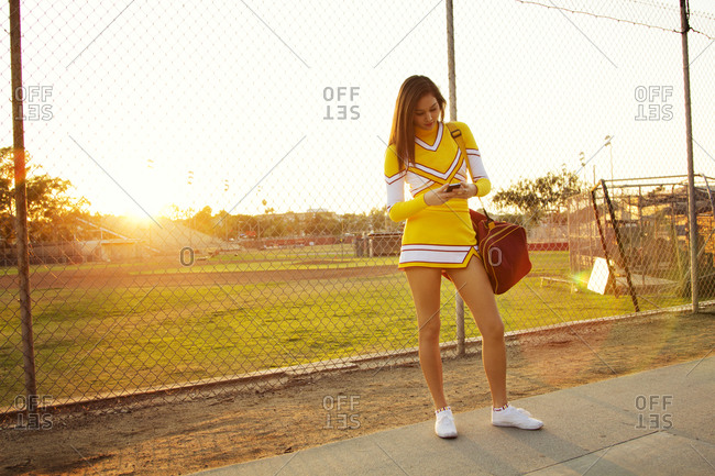 A cheerleader looks at her phone while waiting for a ride