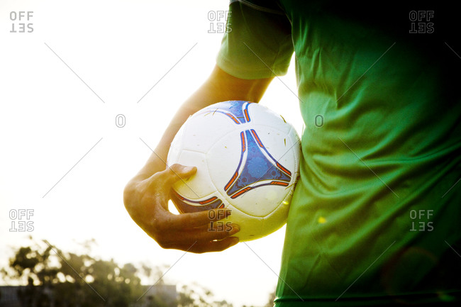 A soccer player holding his ball