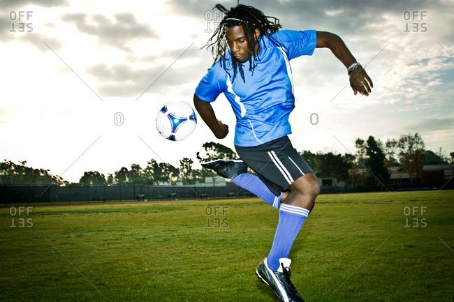 A soccer player kicks his ball behind his back