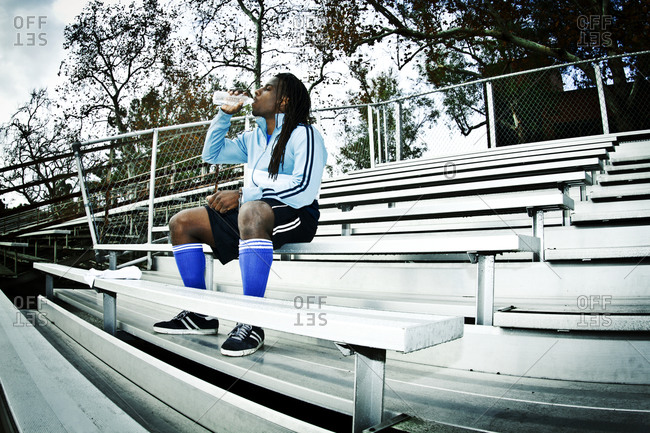 A soccer player takes a break to drink water
