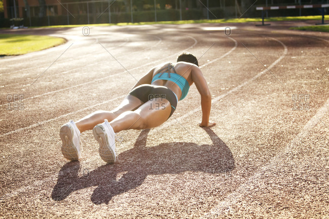 A woman does pushups on a track
