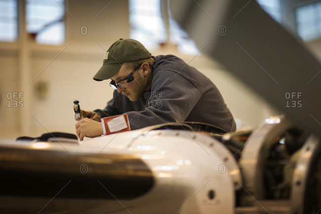 An airline technician repairing airplane engine