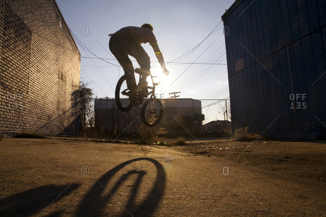 Silhouette of a freestyle biker doing a bunny hop in an alley