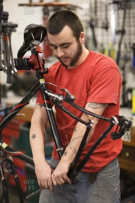 A bicycle repairman working on bottom bracket of bicycle