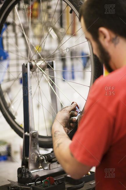 A bicycle repairman tuning wheel spokes