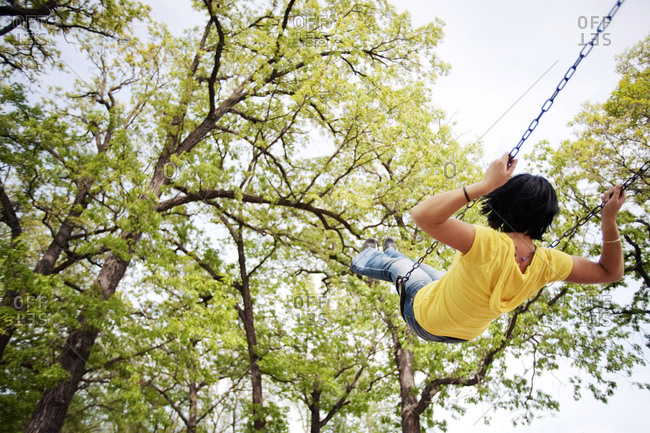 A young woman on swings in a park