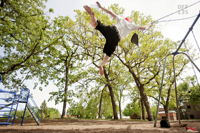 A young man jumping off of a swing