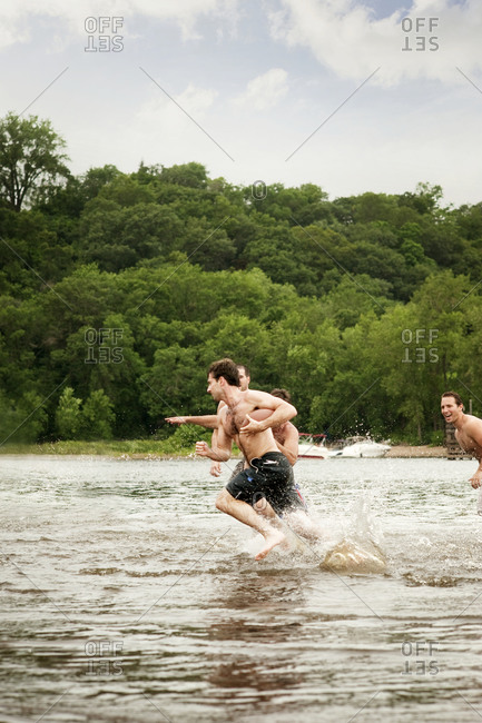 Friends playing football in river