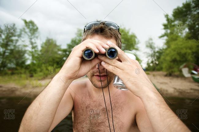 Shirtless man with binoculars at river