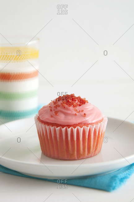A pink cupcake on a plate