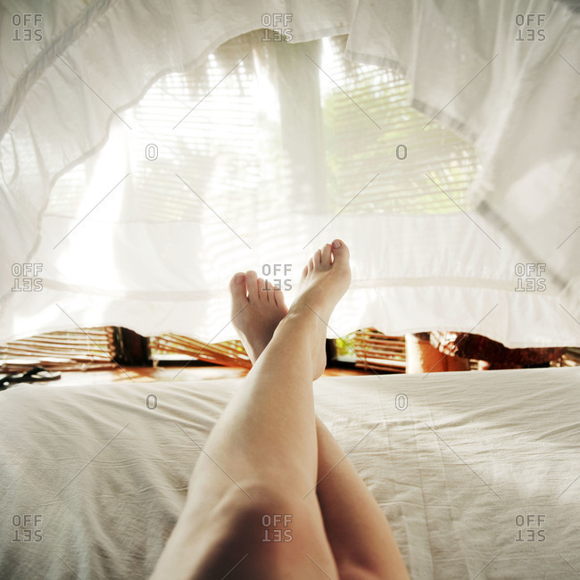 Person relaxing under the sheets
