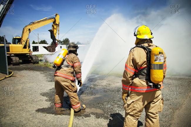 A fireman sprays water on a fire