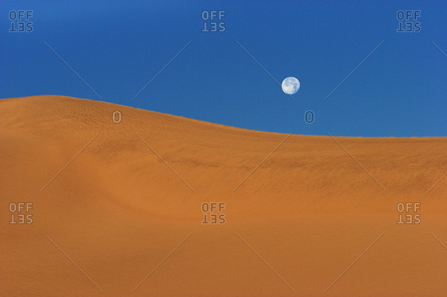 The moon over a sand dune