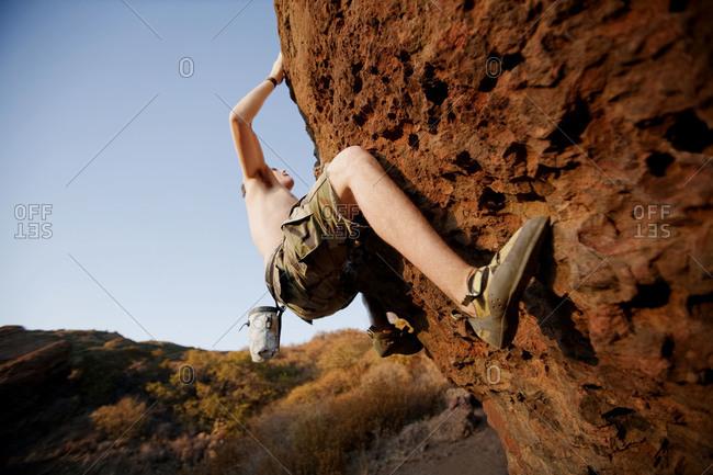 A man climbs a difficult rock face