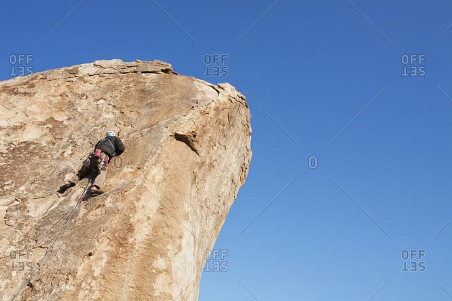 Man climbs rock face in Joshua Tree Park