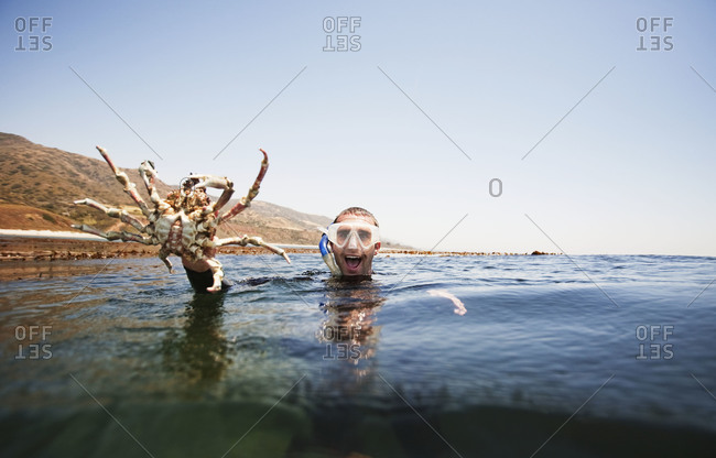 Man holding crab out of the ocean