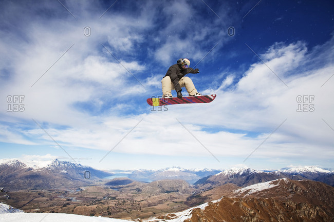 Snowboarder getting big air in New Zealand