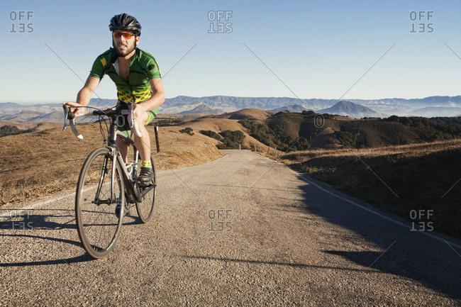 Man climbing hill on bicycle