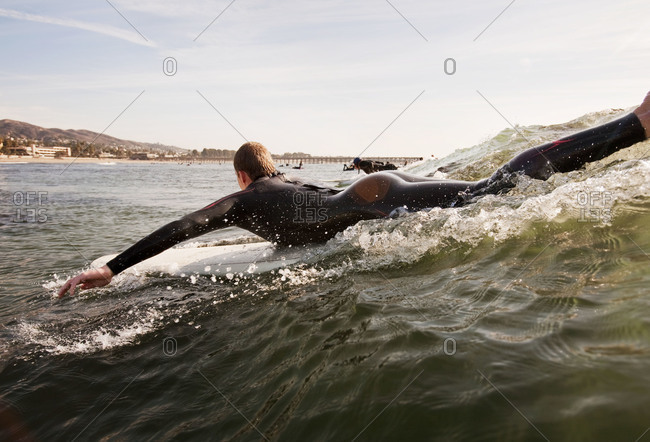 Surfers paddling to catch wave