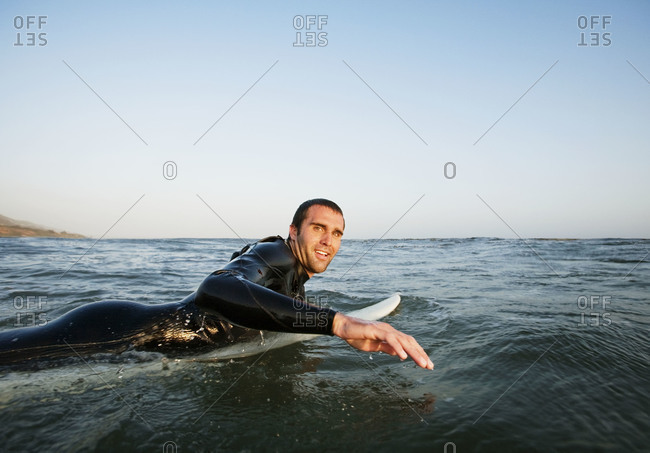 Man paddling out on surfboard
