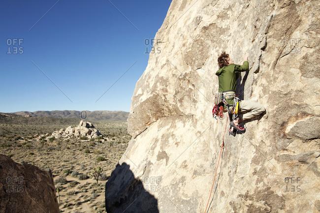 Man climbing rock wall at Joshua Tree State Park