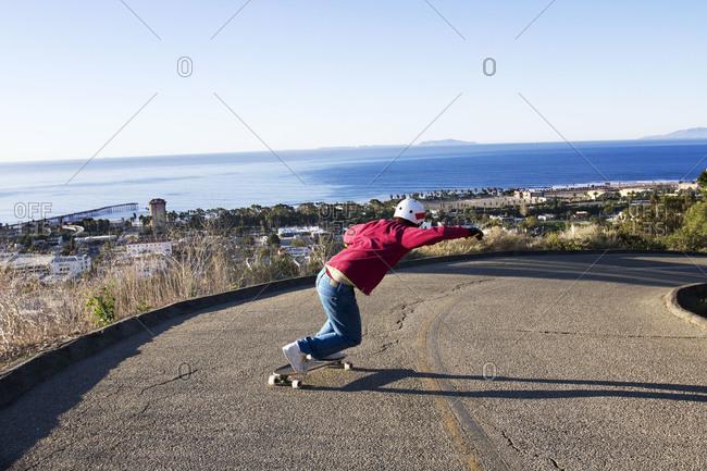Man longboarding down road