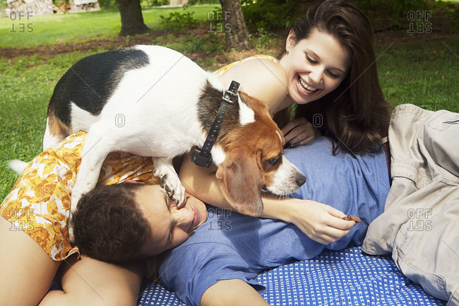 Couple playing with dog on a blanket outdoors