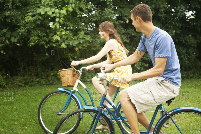 Young couple riding bicycles together