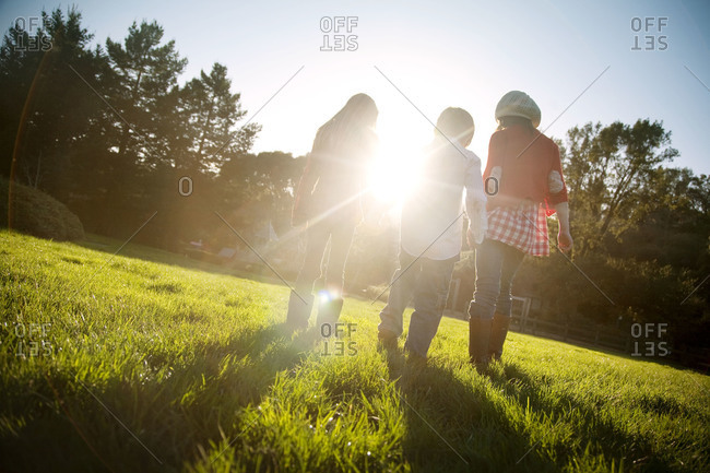 Three girls walk hand in hand in backyard