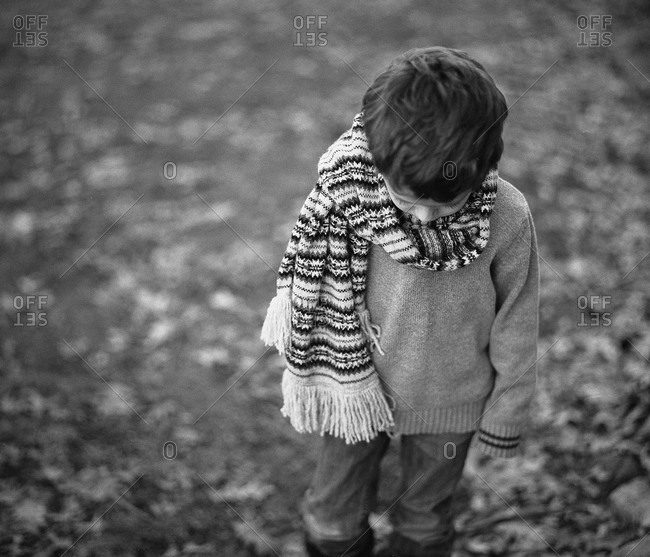 A little boy looks sadly to the ground