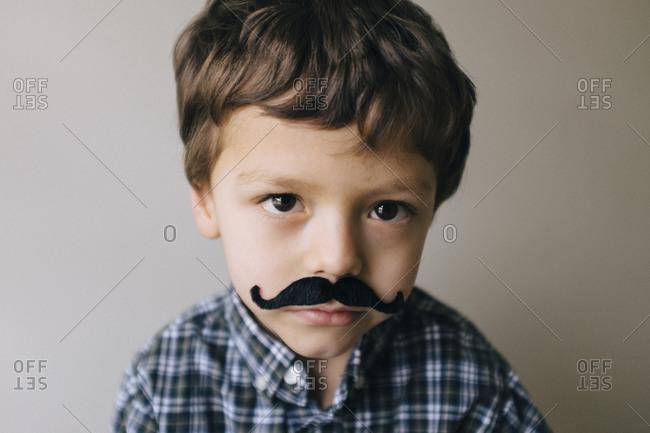 A boy wears a fake mustache
