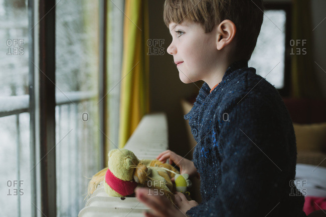 A boy looks out the window at snow falling