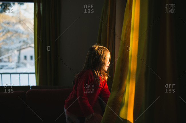A girl looks out of the window at a snowy neighborhood