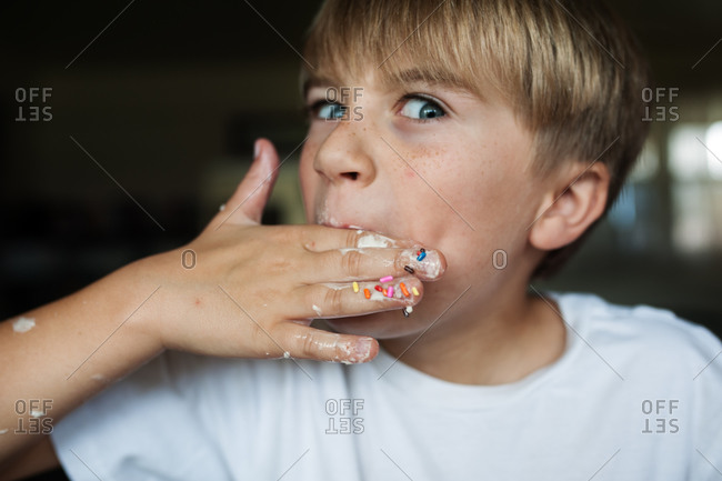 A boy licks ice cream off of his fingers