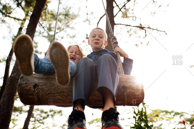 A boy and girl swing on a log