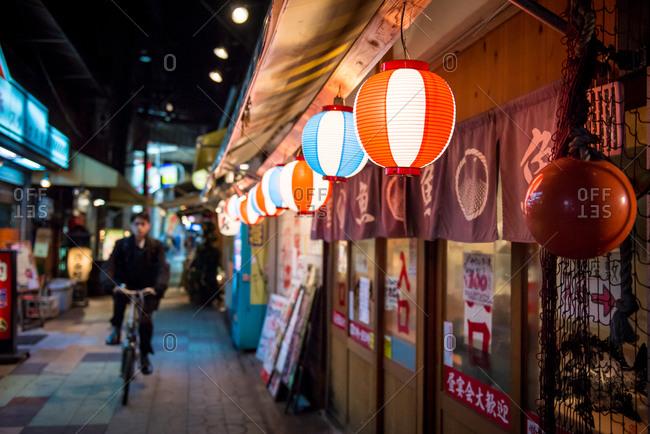 December 25, 2014: Man on bike in narrow street Japan