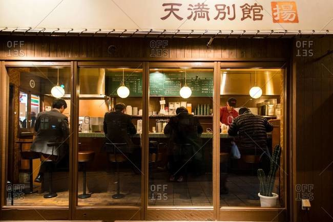Osaka, Japan - December 25, 2014: Men at small diner in Japan
