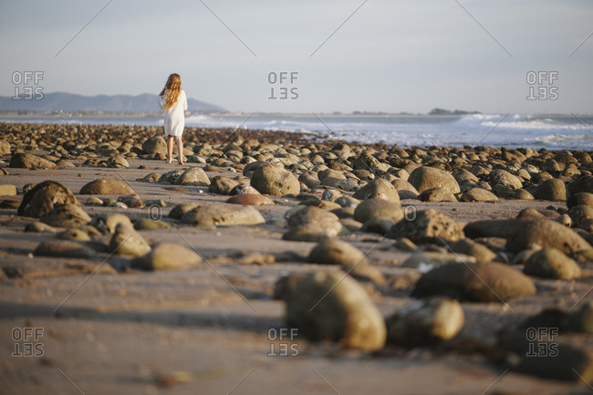 A girl stands on a rocky beach
