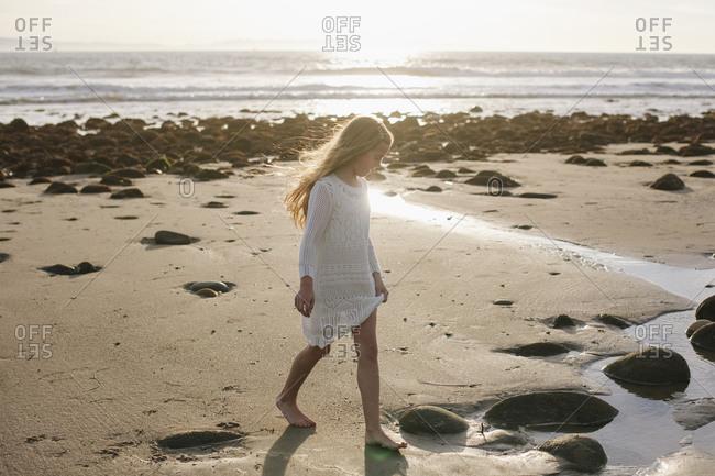 A little girl walks across a rocky beach